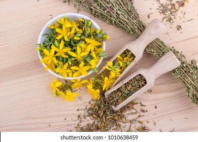 top view on dried and fresh, flowering St. John's wort on a wooden background