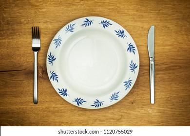 Top view on empty ornamental plate with fork and knife prepared on rustic wooden oak table. Hungry concept,