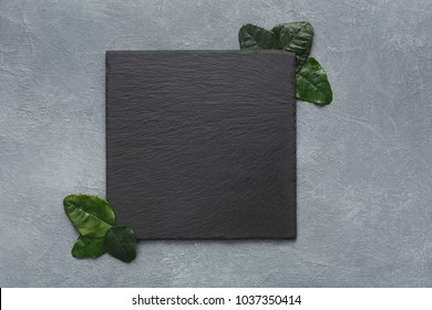 Top view on empty traditional japanese square black slate plate with green leaves on rustic grey background, copy space