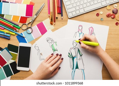 Top view on fashion designer at work. Female hands drawing clothes sketch at her creative workspace, top view