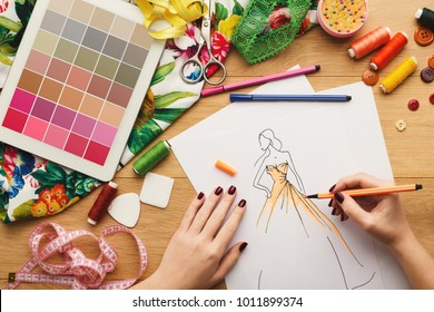 Top view on fashion designer at work. Female hands drawing clothes sketch at her creative workspace and using digital tablet with color swatches on screen, top view