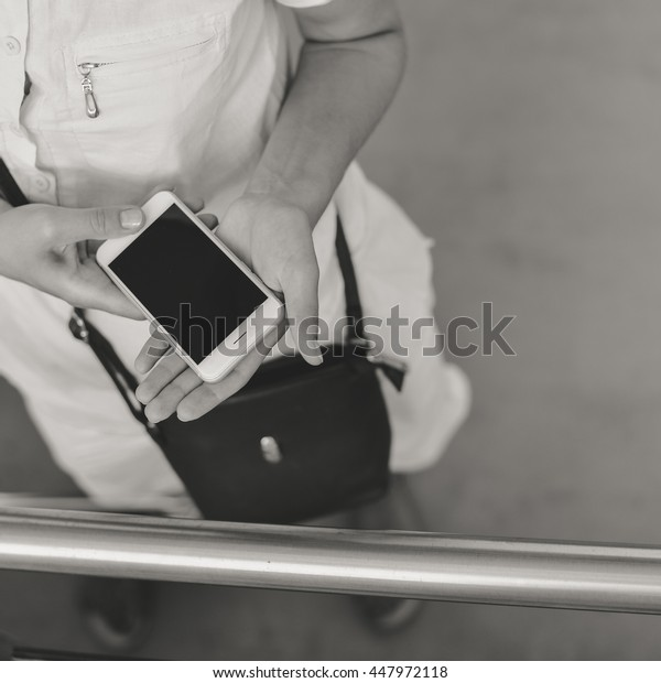 Top view on female using cell phone with shopping cart on window store background. Closeup