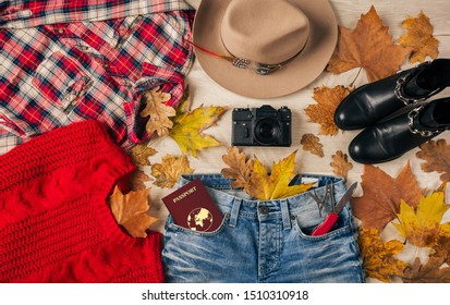 top view on flat lay of woman style accessories, red sweater, checkered flannel shirt, jeans, black leather boots, autumn fashion trend, vintage photo camera, swiss knife, passport, traveler outfit