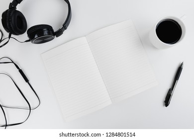Top view on a freelancer/ blogger/ writer workspace. White table top with black headphones, pen, cup of coffe and empty notebook.