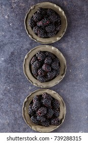 top view on fresh raw blackberries in plate on dark table background
