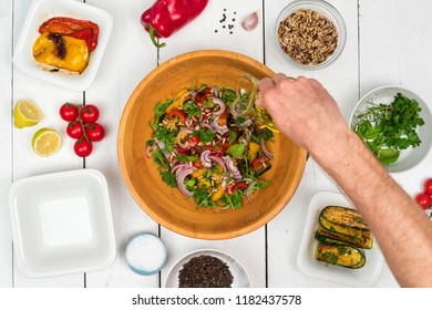 Top view on fresh salad in wooden bowl with food ingredients around on white rustic table.