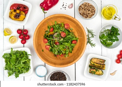 Top view on fresh salad in wooden bowl with food ingredients around the white rustic table.