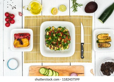 Top view on fresh salad in white bowl with food ingredients around the white vintage table.