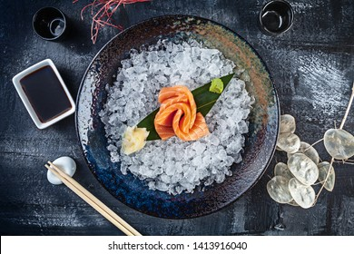 Top view on fresh sliced salmon sashimi served in bowl with ice on dark background. japanese food sashimi. Japan restaurant menu. Copy space for design. Top view seafood. Healthy meal