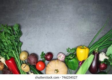 Top view on fresh vegetables arranged around border on grey kitchen countertop.