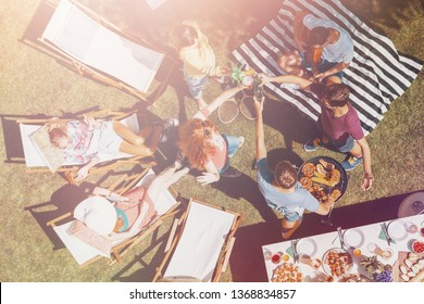 Top view on friends relaxing on sunbeds and dancing during grill party in the garden