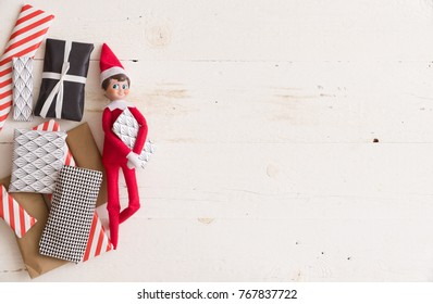 Top view on funny Christmas toy with small gifts for advent calendar on white wooden background.