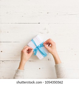 Top view on girl's hands wrapping small Christmas, birthday or any other celebration gift in white paper and decorating it with blue ribbon on white wooden table background.