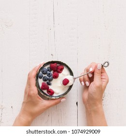 Top view on girl's hands holding a bowl with organic vanilla yogurt with fresh berries. Healthy eating.