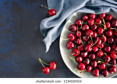 Top view on the gray plate of cherries on dark background with space for your text