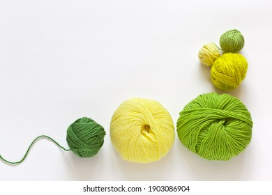 Top view on green and yellow hanks of woolen yarn for hand knitting on a white background. Spring needlework and hobby. DIY concept. Empty space for text. Flat lay, close-up, mock up