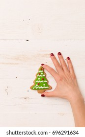 Top view on hand holding homemade Christmas tree cookie on white wooden background. Christmas, holidays, celebration. Baking at home.