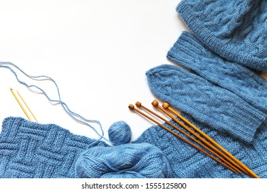 Top view on hand knitted blue mittens, scarf, warm hat  and knit accessories: balls of wool yarn and set of metal and wooden knitting needles on white  background. Place for text, close up, flat lay
