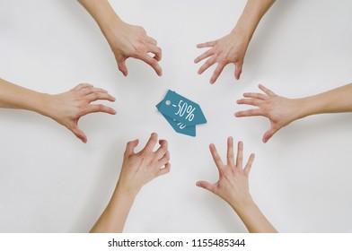 Top view on hands reaching for coupons at a discount. The concept of price reductions, discounts, sales. People want to buy cheap in the store. Fight for discount coupons.