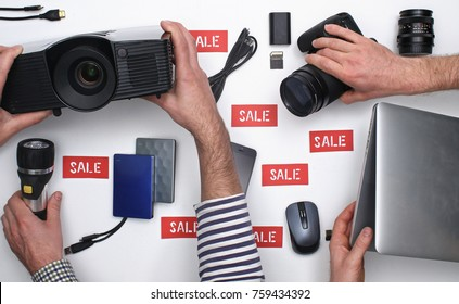 Top view on hands taking electronic products with SALE label on white background. Black Friday concept.