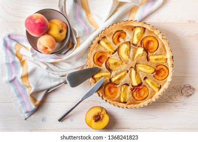 Top view on Homemade open peach pie on white wooden background with knife and spatula for pie.