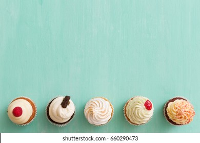 Top view on homemade vanilla, bluebery, lemon, chocolate cupcakes in row on turquoise retro wooden background. Healthy food, snack for birthday party or celebration