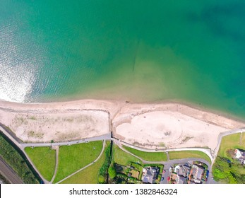 Top view on houses near beach on coast of Irish Sea in Holywood Northern Ireland. Countryside view against clear blue sky