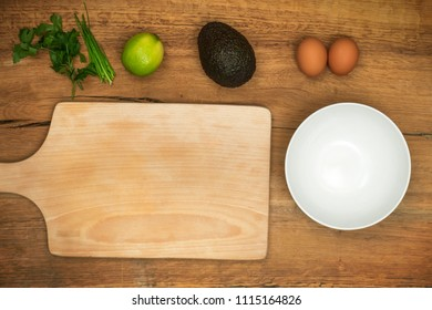 Top view on ingredients for avocado with eggs salad recipe on rustic wooden table.