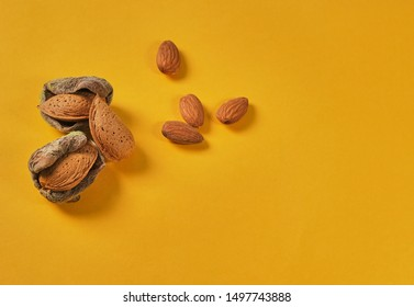 Top view on just from the branch nuts, unshelled and shelled Almonds. Flat lay with food and copy space. Minimal modern composition on yellow background.