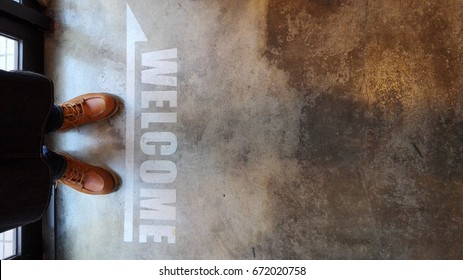 Top view on legs in leather shoes and jeans on aged floor with an inscription Welcome. barber shop