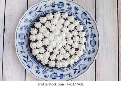 Top view on low height dark chocolate cake with whipped cream on a Blue Onion Plate