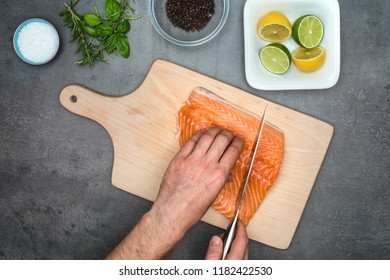 Top view on male hand with knife cutting steak from salmon fish on wooden cutting board with fresh food ingredients around the grey kitchen countertop.