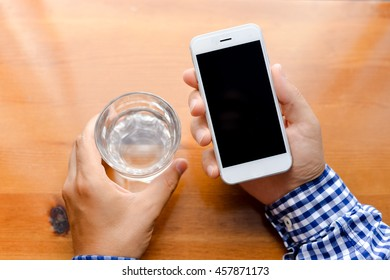 Top view on man working on mobile phone, hands and glass of water on wooden desk background.