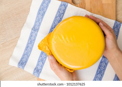 Top view on man's hands holding a head of fresh organic cheese in yellow vacuum package. Food concept