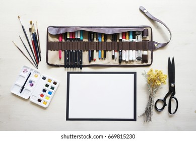 Top view on mock up of white blank paper on white wooden table background with markers in leather case, dried yellow flowers, brushes, black scissors, and watercolor palette.