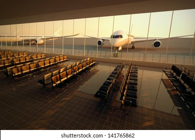 Top view on a modern airport terminal with black leather seats at sunset. A huge viewing glass facade with a passenger aircraft behind it.