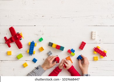Top view on mother's and child's hands playing with colorful plastic bricks, toys and building from them. Learning by playing.