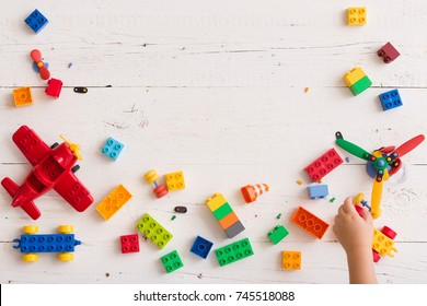Top view on multi-color toy bricks and child hand picking them on white wooden background. Toys on the table.