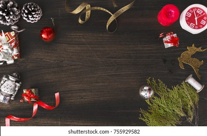 Top view on nice Christmas gift wrapped in white gift paper, Christmas tree decorations on dark wooden background. New Year holiday