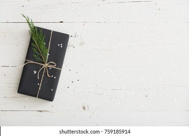 Top view on nice Christmas or birthday gift wrapped in black paper and decorated with cord and tree brunch on white wooden background.