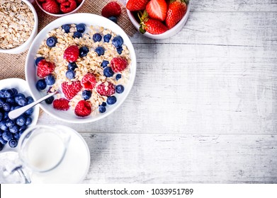 Top view on oat flakes with milk and forest fruit. Oat flakes, blueberries and raspberries, strawberries, lavender on white table.