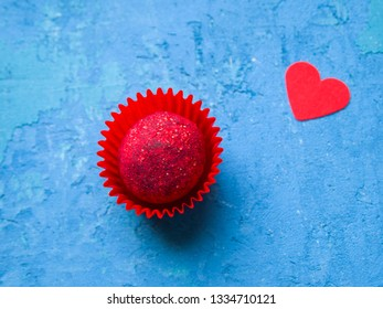 Top view on one crimson chocolate truffle decorated with raspberry sprinkle and one red heart (symbol of love). Romantic concept.