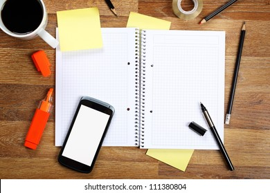 Top view on opened notebook, smartphone, highlighters, sticky note, cup of coffee and other equipment on wooden office desk.
