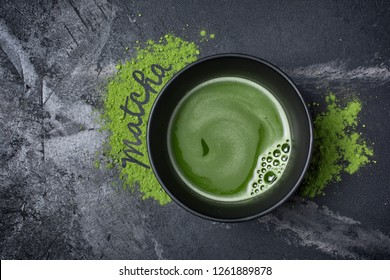 Top view on organic green matcha tea in ceramic cup with lettering on black marble background