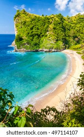 Top view on paradise azure beach with rocky mountains, green palm trees and clear water of Indian ocean at sunny day / A view of a cliff in tropical island Bali Indonesia / Bali, Indonesia