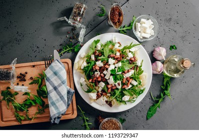 Top view on pasta dish with arugula and white feta cheese on a dark black stone. White pasta with rucola, feta and fried bacon with ingredients. Lunch concept, food photography.