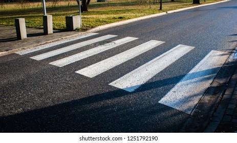 Top view on pedestrain crossing, wet asphalt and zebra crossing, crosswalk