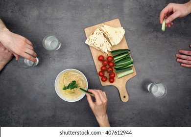 Top view on people eating Hummus (Houmous) oriental recipe with pita bread and fresh vegetables.