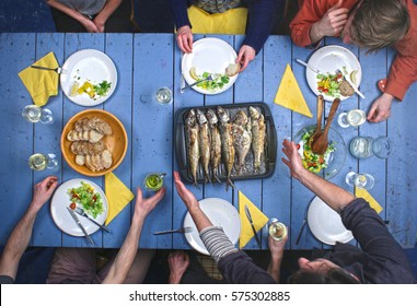 Top view on people eating grilled fish with vegetable salad and drinking vine.