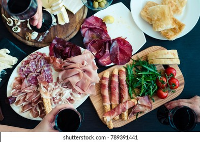 Top view on people eating and toasting with glasses of red wine. Friends or family different ages enjoying dinner concept. Table full of mediterranean appetizers. Assorted Italian food set.